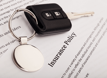 A set of car keys on top of a piece of paper titled Insurance policy