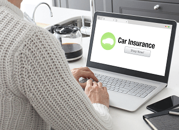 Woman has laptop open to a shop now for car insurance website